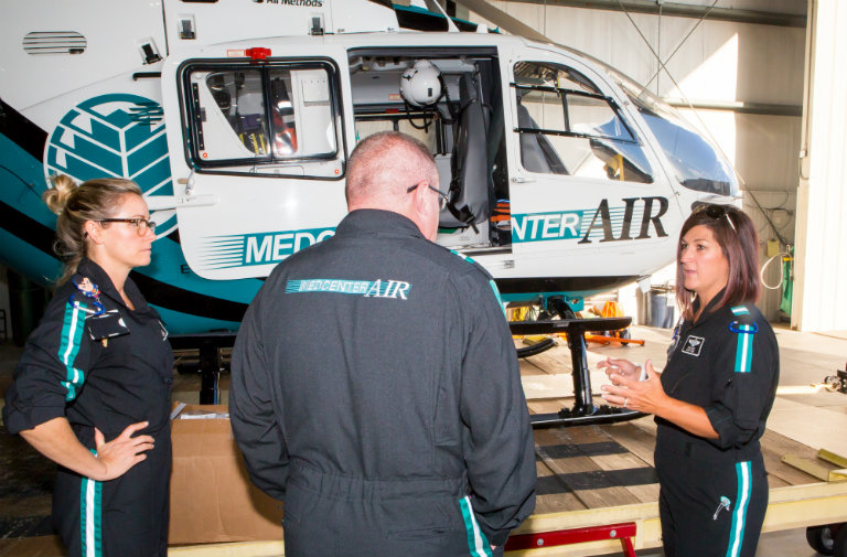 Atrium Health's MedCenter Air nurses (from left) Liz Soriano, RN, Brian Huss, RN, and Erica Cook, RN, prepare a helicopter to be deployed ahead of Hurricane Florence.