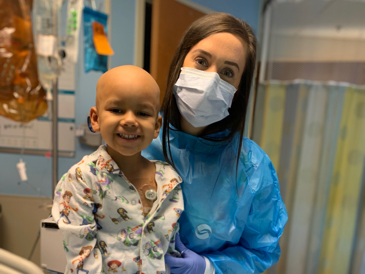 Sarah with one of her sweetest patients, Dominic. He's five years old, full of laughter, and currently getting treatment for Burkitt Lymphoma.