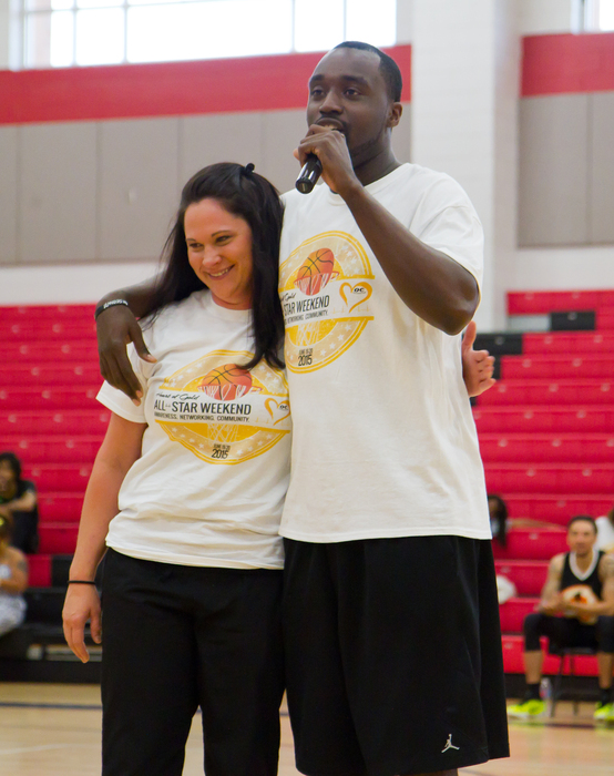 Omar Carter, right, speaks to a crowd while embracing Kelly Thomas, a cardiac intensive care unit nurse at Carolinas Medical Center, who helped save his life when he collapsed playing basketball two years ago.