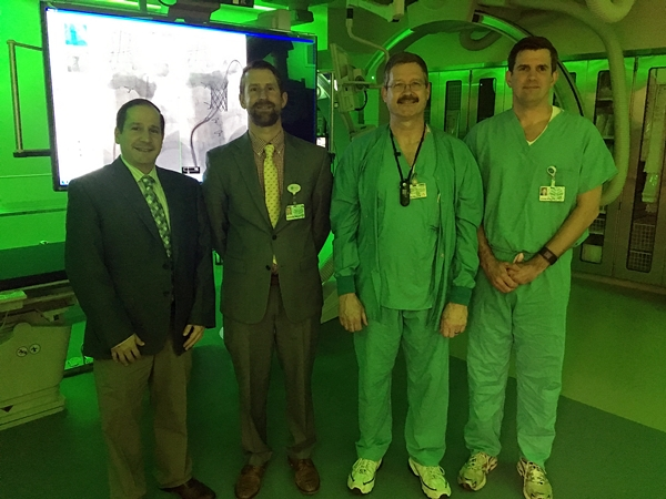 Joseph Paolillo, MD, pediatric cardiologist, Steve Wright, AVP of cardiovascular services, Tom Wilson, technical operations manager of surgical services, central division, and Chan Roush, VP, central division operations, review the new pediatric catheterization lab at Levine Children's Hospital.