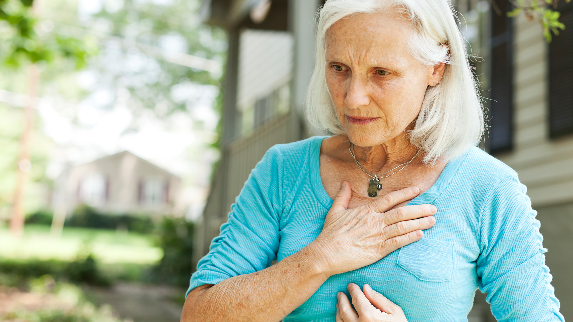 Woman suffering from heart burn holding her chest